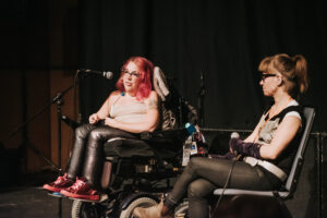Two people sit at the front of a stage. One of them has red hair, leather trousers, and sits in a wheelchair speaking into a microphone.