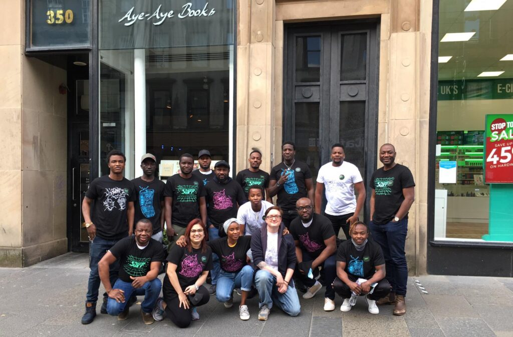 A group of people, mostly members of LGBT Unity, are posing for a photo on the street in front of buildings, one of which has a glass window and the words Aye-Aye Books written.