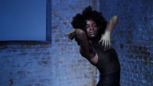 A black person with an afro and wearing a tight black outfit is dancing, appearing absorbed in the moment. In the background is a brick wall. All is bathed in blue light.