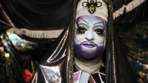 A white person wears an elaborate habit made of shiny material and a jeweled bee design on the forehead. They wear white make-up covering their face with a purple beard and lips, and the blue and pink of the trans flag elsewhere on their face plus big black eye make-up.