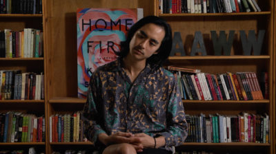 An Asian-American man sits wtih legs crossed, his head titled thoughtfully to one side, looking down. He has long black hair and wears a patterned shirt. In the background are bookshelves.
