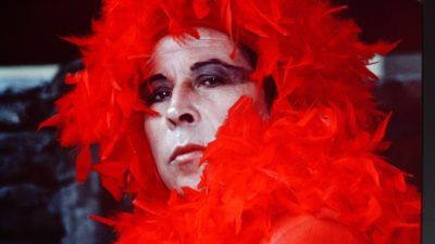 A white person, Pedro Lemebel, with white facial and dark eye make-up stares at the camera. His head is engulfed by red feathers.