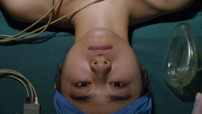 A Chinese woman's face in close is seen upside down as she lies on a green sheet in a hospital bed. She wears a blue surgical cap and wires are seen across her bare shoulders.