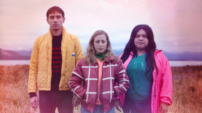 A white man with short dark hair and a yellow jacket, white woman with long blonde hair and a red and white striped jacket, and Latina woman with long dark hair and luminous pink jacket stand in a field looking directly at the camera.