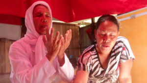 Two Bugis women from southern Indonesia sit next to each other in a wooden building with red awning. One has a white shirt and headscarf and appears to be in prayer. The other woman wears a black and white tshirt with a tiger on it and is looking down.
