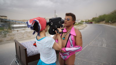 A white woman with dark hair in a pink and white headscarf and a white and green outfit holds a 16mm camera up to a white man with short blond hair, wearing bright make-up, a pink, white, and black skimpy wrestling outfit, and a green medalion. Behind them is a stretch of road.