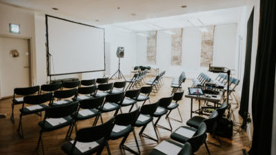 A bright room with sunlight streaming in the windows. In the room are rows of chairs and a projector facing a screen.