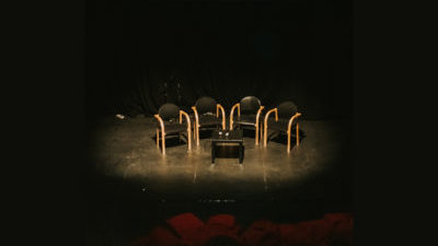 Four black and wooden chairs and a small black table sit ominously in a spotlight surrounded by black.