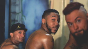 Two black men and one white man with bare shoulders are pictured in a row looking intensely in the direction of the camera.