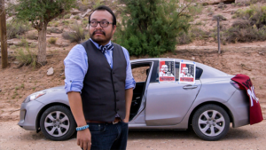 A brown man in light purple shirt, waistcoat, and tie with short dark hair, beard, and glasses stand with his hand in his pocket, looking up to the side. Behind him is a silver car with election posters on it, desert, and trees.