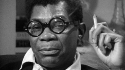 Black and white close up of a black man, Jason Holliday, gazing directly at the camera with a sly perhaps annoyed look. He has short black hair and glasses, and holds a cigarette in his hand.