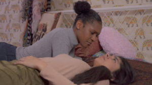 A black person with hair up in a bun and blue jumper lies on a bed leaning over a brown person with long dark hair and a pink jumper. There is a pink cushion and flowery wallpaper behind them.