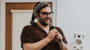 A white person with short dark hair, a beard, glasses, and wearing a snow leopard santa hat grins, speaking into a microphone.