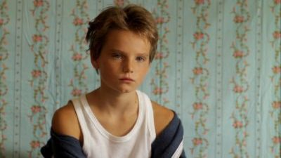 A white child with short, messy blond hair, wearing a white vest and blue tracksuit top falling off their shoulders, stares sullenly ahead. A wall with light green and pink flowered wallpaper is behind them.
