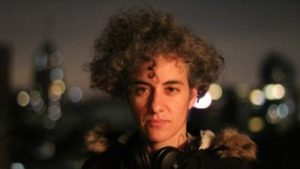 A white person with big curly mousy hair, headphones round their neck, and a big jacket looks direct to camera. Behind thmem are blurred city lights.