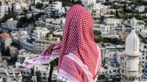A figure with a pink headscarf covering their top half completely with their back to camera looks out across a bright city filled with tall white buildings.
