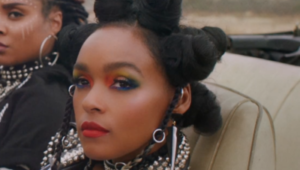 A black woman - Janelle Monae - is in close up looking just beyond the camera. She has black hair in pigtails and wears multi-coloured eye make-up, bright red lipstic, and a pearl collar. Just behind her another black woman can be seen. They are both sitting in an open top car.