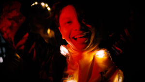 A white person bathed in red light and shadow looms out of the dark, grinning with light playing about them.