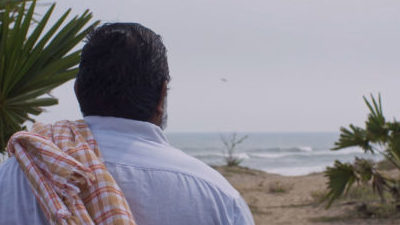 A brown man with his back to camera, short dark hair, a white shirt, and red and white checked clothing item over his shoulder, looks out to sea from a sandy beach with palm trees.