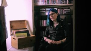 A white person with long blue hair and glasses, a black leather jacket, sitting down. There is a bookshelf with DVDs and CDs behind them and an open box full of records to their right.