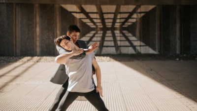 Two people stand legs apart in a dancing pose surrounded by concrete, behind them a reflection caused by sunlight and windows. One person with short black hair and a dark jacket and trousers has their arm around the neck of the other person, who has short dark hair, a grey tshirt, and dark trousers, in dance pose.