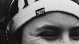 Extreme black and white close up of the face of a white person scrunching up their eyes as if smiling, wearing a woolly hat and headphones.