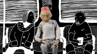 A stop motion figure of a brown person with short pink hair, grey jumper, and jeans sits with hands on lap looking down in a rail carriage. Next to them are drawn black and white figures.