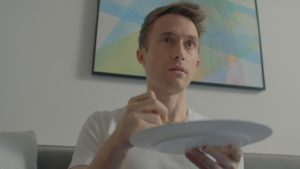 A white man with short mousy hair sits on a sofa eating something unseen off a plate he is holding. He looks startled. Behind him is a light wall with a white, blue, and green framed picture on it.