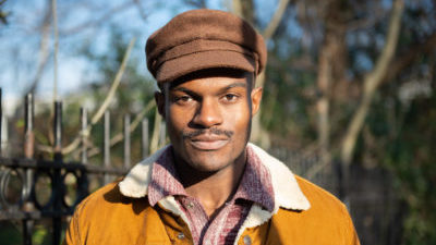 A black man looks directly at the camera. He has a small moustache and is wearing a brown flat cap, red and white shirt, and tan with white collar jacket. Behind him is a park railing and trees.