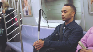 A black man sits on a subway carriage seat. He has short black hair, his eyes are closed, he holds a white cane, and he wears a dark jacket.