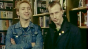 Grainy image of two men standing in front of book shelves. They both have short blonde hair. One wears a demin jacket and is crossing his arms and smiling. The other wears a black jacket with collar turned up and is looking to the side.