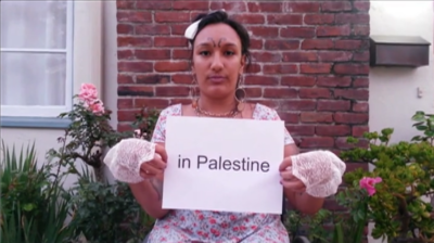 A person with dark hair and long earrings wearing a flowery dress and lace gloves is in front of a brick wall and flowers. They hold a sign which reads, 'in Palestine.'