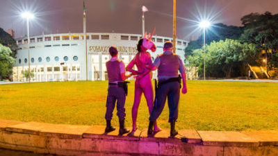 From behind two policemen stand on either side of a naked man with a unicorn mask on a small wall in front of grass with night lights and a stadium in the background.