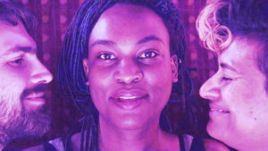 A Black person with braids and a slight grin is in close-up looking directly to camera. On either side looking at them and smiling are a White person with a dark beard and a brown person with a bleached forelock and nose ring. All are bathed in pink and purple light.