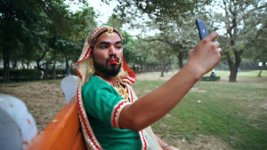 A person wearing Hindi sari and jewellry with a beard and bright red lipstick sits on a park bench, taking a selfie.