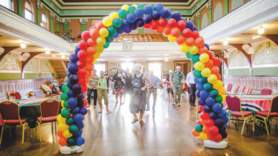 A ballroom filled with people being led in a dance with tables and chairs round the side and a rainbow arch made of balloons at the front framing them.