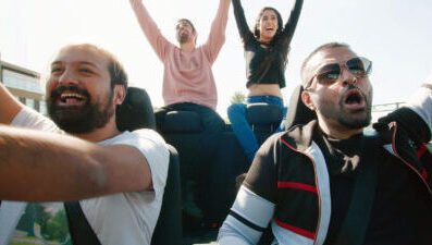 Four people are in a moving, open topped car with their hands in the air, smiling and shouting in a celebratory way.