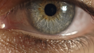 Extreme close-up of a human eye with a greeny blue colour and moisture in the corners suggesting tears.