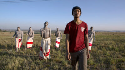 A Black man with red tshirts and a dark woolly hat is striding forward on a grassy plain with five other Black men covered with white powder and traditional Xhosa skirts and sticks walking behind him.