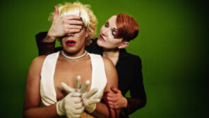 A white person with short red hair wearing a black suit jacket stands with her hand over the eyes of a second white person with blond hair in curls, red lipstick, a white bra-crop top, and rubber gloves.