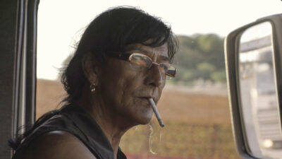 A white woman with long dark hair, glasses, a dark vest, and a cigarette hanging out her mouth sits in a truck with a large wing mirror beside her face and a blurred countryside landscape in the background.