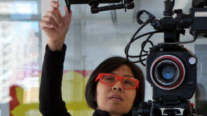 Lana Lin, a woman of colour with short black hair, bright red glasses, and a black top is standing next to a large camera with her hand up adjusting the monitor.