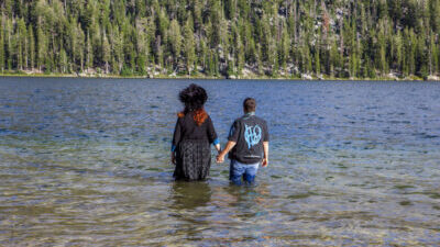 Two people, one with long bright red hair and dramatic black attire and one with short hair dressed butch casual, stand hand in hand knee deep in a lake with a hill filled with trees beyond it.