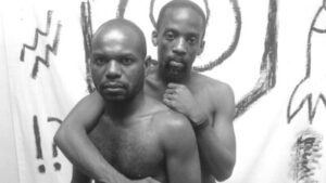 Two Black men are naked from the waist up in front of a white sheet with sketches of rocket and other items on it. One has an arm around the other's shoulder and they both look directly at the camera.