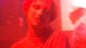A blurry red and pink image of a person lost in clubbing euphoria.