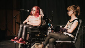 A woman with long red hair, leather trouser, and red shoes sits in a wheelchair talking into a microphone. Another woman with light brown hair, glasses, and a black top sits beside her.