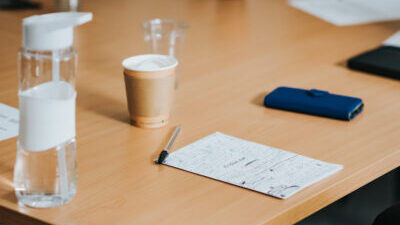 A piece of paper with lots of notes on it sits on a wooden table top alongside a pen, phone, and empty coffee cup.