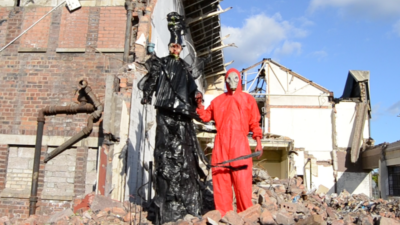 Two figures, one wearing a red hazmat suit and gas mask and the other wearing an elaborate black plastic head to toe outfit including a tall black hat stand amongst buildings in rubble.