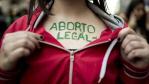 "Close-up of a person with long dark hair's chest. They are holding open their red zip-up jacket to reveal green writing on their chest which reads, ""Aborto Legal."""
