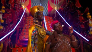 Two Black people with queer, Afrofuturist gold, silver, and multi-coloured outfits stand at the bottom of a set of futuristic, theatrical red stairs. One person leans on the other's shoulder, who holds up their fingers in a peace sign.